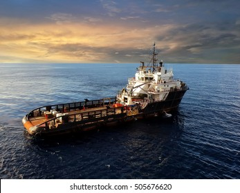 Offshore cargo supply ship with dramatic sky during sunset
