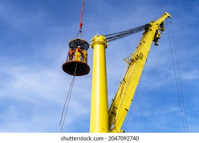 Offshore crews being transferred to a constrution work barge via a personal transfer basket at an oil field