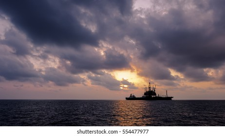 Offshore drilling platform and FPSO ship silhouette in sunset offshore oil field.
