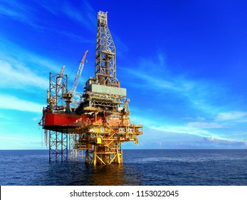Offshore drilling rig work on oil well production platform with beautiful blue sky and white cloud