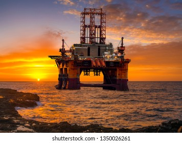 Offshore drilling in rocky coasts of the ocean at the time of the rising of the sun