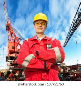 Offshore engineer, looking proudly, standing on the deck of an industrial vessel at the docks