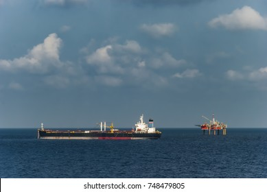 Offshore facility oil and gas production industry. FPSO ship and drilling rig view with blue sky bakcground