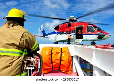 The offshore fireguard standing by on the helideck with the helicopter waiting for passengers