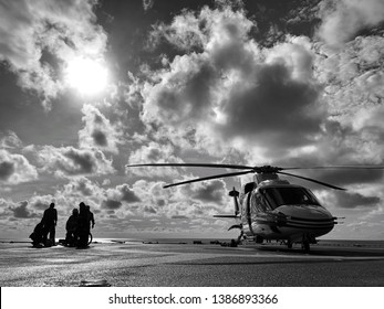 Offshore Helicopter and its flight and ground crew cloudy sky,The helicopter landed on the rig, sea, changing working group, working on the rig, to return home. Offshore helideck black and white photo