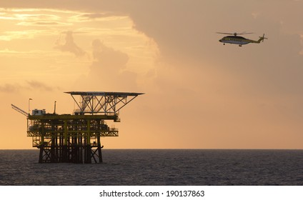 An offshore helicopter for transporting roughnecks approaches a rig