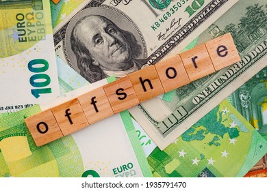 OFFSHORE inscription on wooden cubes on the texture of us dollars and euro banknotes