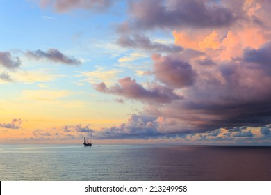 Offshore jack up drilling rig in the middle of the ocean during dramatic sunset time