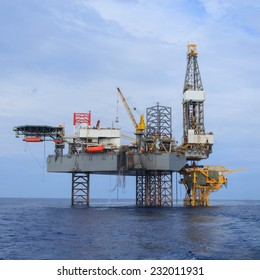 Offshore Jack Up Drilling Rig Over The Production Platform in The Middle of The Sea - View from Crew Boat