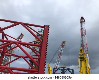 Offshore jack up rig or offshore jack-up oil and gas drilling rig with crane operation under a blue sky