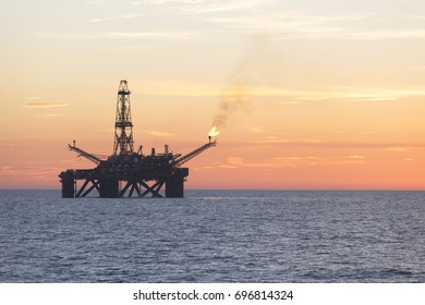 Offshore Jack Up Rig in The Middle of The Sea at Sunset Time