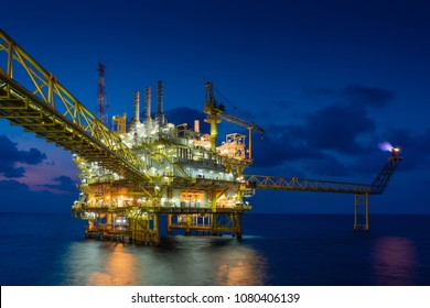 Offshore oil and gas construction platform in sun set where produced raw gases and crude for set to onshore refinery and petrochemical plant, Power and energy business industry.