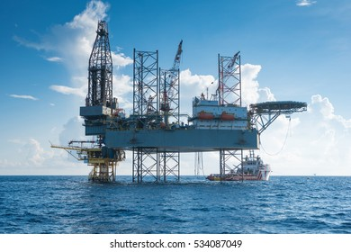Offshore oil and gas drilling rig working on new wellhead remote platform to completion on gas and crude oil well, oil and gas exploration and production in the gulf of Thailand.