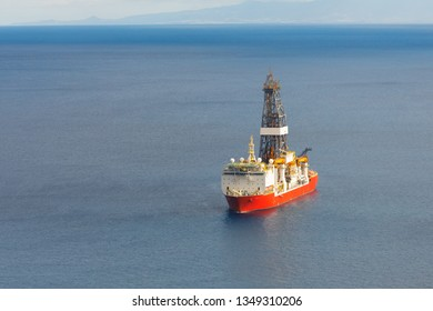 offshore oil and gas drillship, blue sea background, aerial view