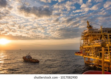 Offshore oil and Gas processing platform, petrolium industry to treat raw gases and sent to onshore refinery with supply boat in sunset time.