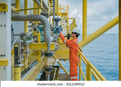 Offshore oil and gas worker operating touch screen of gas flow meter coriolis type to reading and adjusting parameter of flow element and used radio to talk with central control room operator.