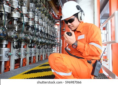 Offshore oil and gas worker used radio at wellhead remote platform to talk with board man at control room, Oil and gas industry, operator monitor production process, routine daily record.