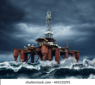 Offshore Oil Platform standing in the middle of ocean sea water during dark cloudy day, with high waves and storm