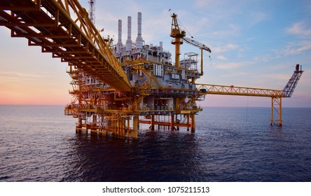 Offshore oil and rig platform in sunset  time.