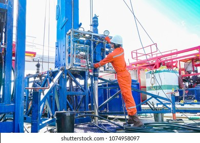 Offshore oil rig worker inspect and setting up top side tools for safety first in hazardous area to perforation crude and gases production well. Power and energy business industry.