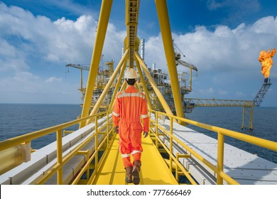 An offshore oil rig worker walk to oil and gas central facility to working in process area, maintenance and service operation at hazardous area.