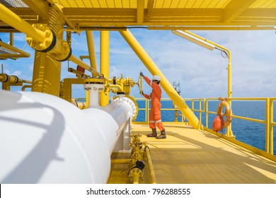Offshore oil rig worker wear helmet gloves safety glass and coverall suite opening valve at oil and gas central processing platform, maintenance and service jot at offshore power and energy industry.