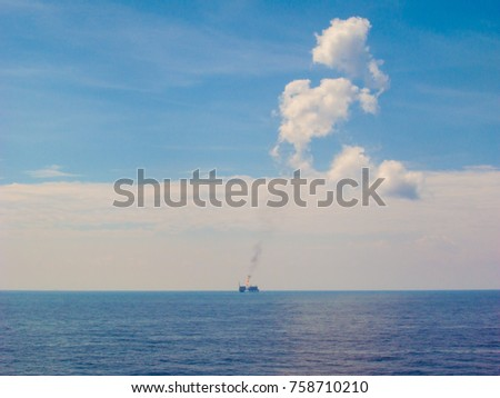 3c14b6737780 Offshore production flare with orange flame while release the smoke with  the clear blue sky background