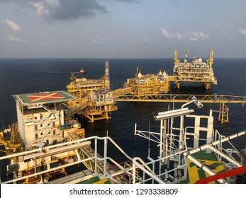 Offshore rig platform or Offshore oil and gas Accommodation Platform or Living Quarter and Production plant and gangway with a calm sea, supply boat and blue clear sky.