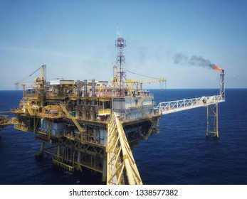 Offshore rig platform or Offshore oil and gas Accommodation Platform or Living Quarter and Production plant with a calm sea and blue clear sky with active flare boom and gangway with remote platform
