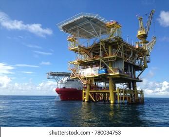 Offshore satellite platform and marine vessel alongside  to the offshore platform.