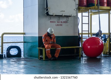 Offshore Terengganu, Malaysia. Circa August 2015. Able-bodied seamen taking a rest on a bench at a construction barge after performing personal transfer using a boat landing at ExxonMobil oilfield