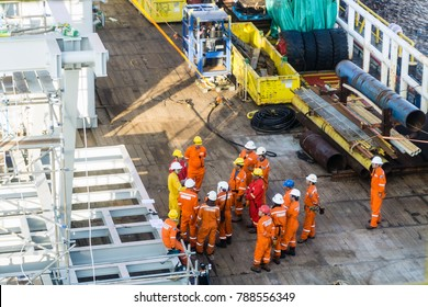 Offshore Terengganu, Malaysia. Circa August 2015. A group of offshore workers having a toolbox talk on a main deck of a construction barge prior to heavy lifting activities