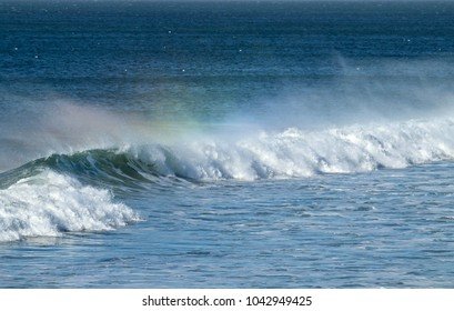 offshore waves creating a rainbow in the spray