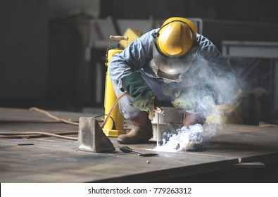 Offshore welder working in his workshop with full protective equipment