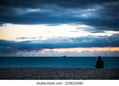 Offshore wind farm at dusk viewed from the beach