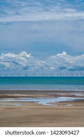 An offshore wind farm sits on the horizon between low white stratocumulus clouds, higher cirrus clouds, a calm English Channel and a sandy beach at low tide. Littlehampton, West Sussex, England.