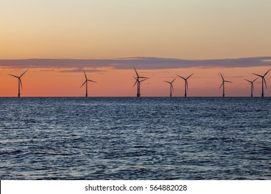 Offshore wind farm turbines caught in the orange glow of sunrise. Beautiful contrast with the blue sea. A great image to convey conservation via renewable energy sources.