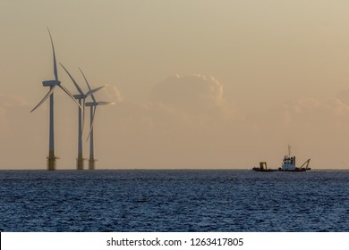 Offshore wind farm turbines on the horizon with passing maintenance  ship. Green energy production and environmental conservation from sustainable resource. Windfarm off the East coast of UK.