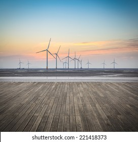 offshore wind farms in sunrise with wooden floor , renewable energy background.