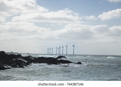 Offshore wind generator. Wind turbines, a wind power plant that looks like waves on the ocean waves, are churning out electricity in the ocean breeze.