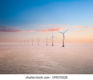 offshore wind power plants in sunset , clean energy background