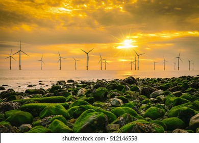 Offshore Wind Turbine in a Wind farm under construction off the England coast at sunset.