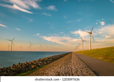 Offshore Windmill farm in the ocean   , windmills isolated at sea on a beautiful bright day, wind mills during sunset in the Netherlands