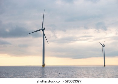 Offshore Windmill farm Westermeerwind during sunset with stormy clouds by Urk