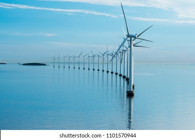 offshore windmill park alternative energy. windmills in the sea with reflection morning
