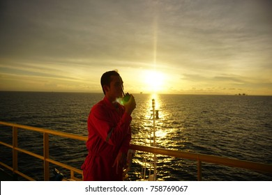 Offshore worker communicate with Marine Captain using radio.Beautiful sunset sky at the background.