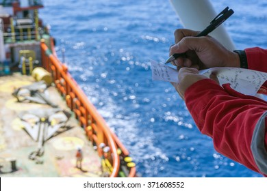 Offshore worker taking note while performing anchor handling operation at Terengganu oilfield, Malaysia