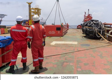 Offshore workers complete with Personal Protective Equipment (PPE) standing on main deck holding tag line and ready to perform lifting red cargo basket using crane.