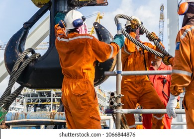 Offshore workers installing big sling onto crane block in preparation of heavy lifting of structure frame from a construction barge to oil platform