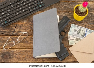 Ofiice table with headgun and office materials at the rustic table with us paper currency ( mobbing )